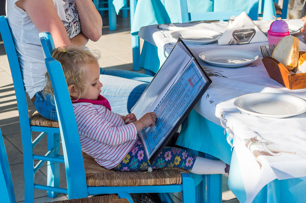 Little Anna reading the menu at a tavern in Potos, Thassos, Greece