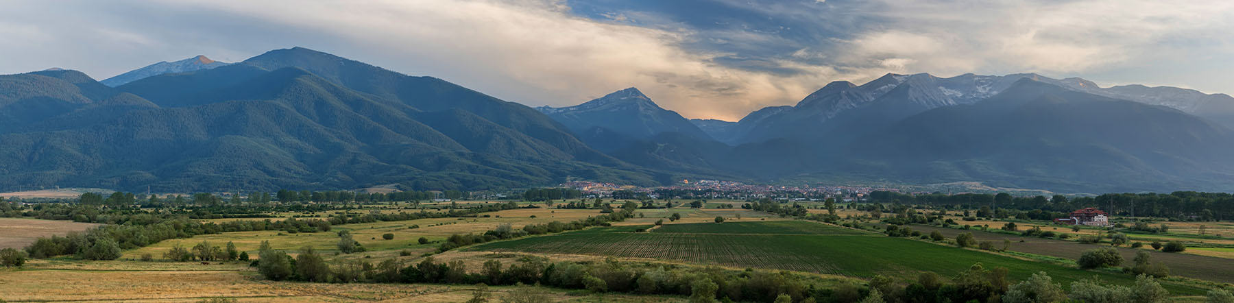 The view towards Bansko and Pirin mountains from the Kameno area near Banya village, Bulgaria. Hotel Seven Seasons can be seen right on the photo