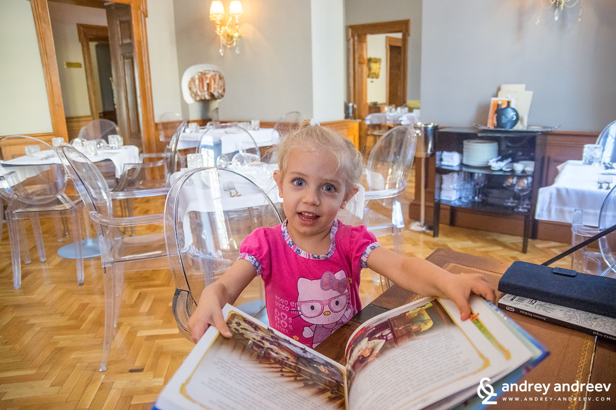 Little Anna reading books athe the kids' place at Club Pouchkine, Sofia, Bulgaria
