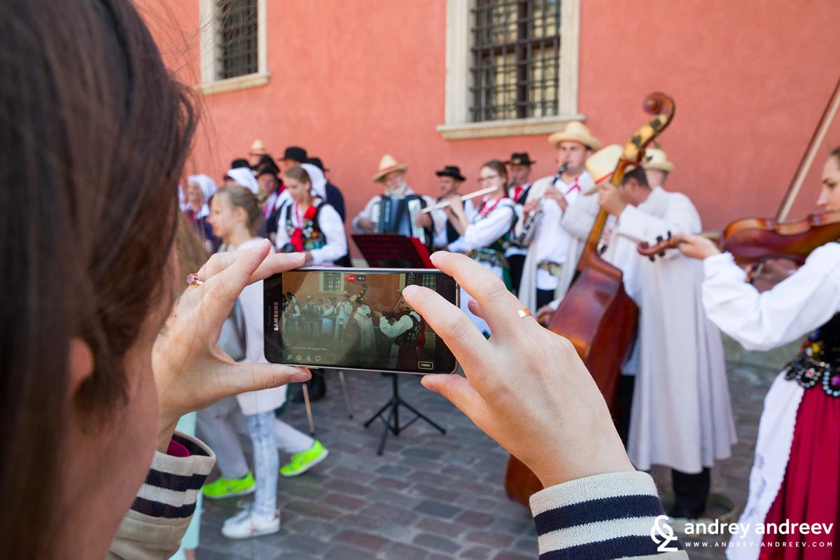 Maria taking photos of performers in front of the Royal Castle in Warsaw