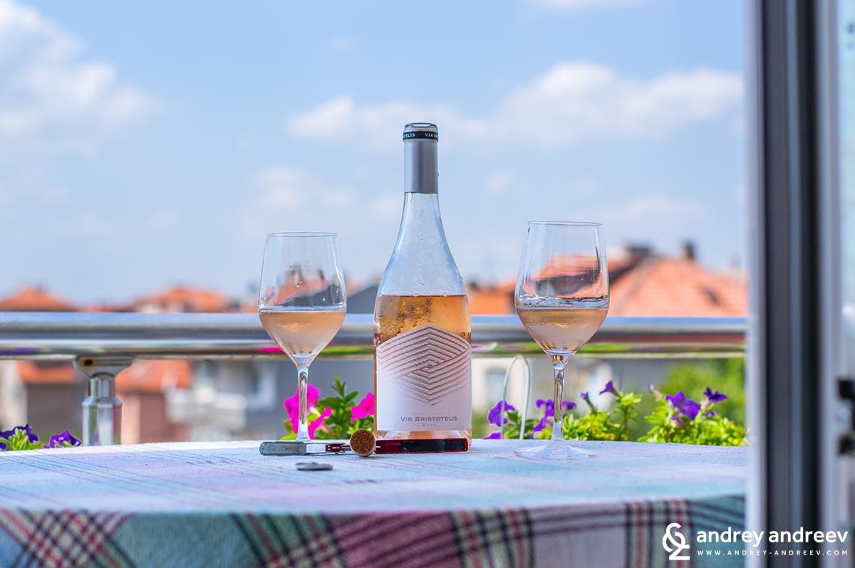 Бутилката розе Виа Аристотелис на приятната гледка на шарен бургаски квартал