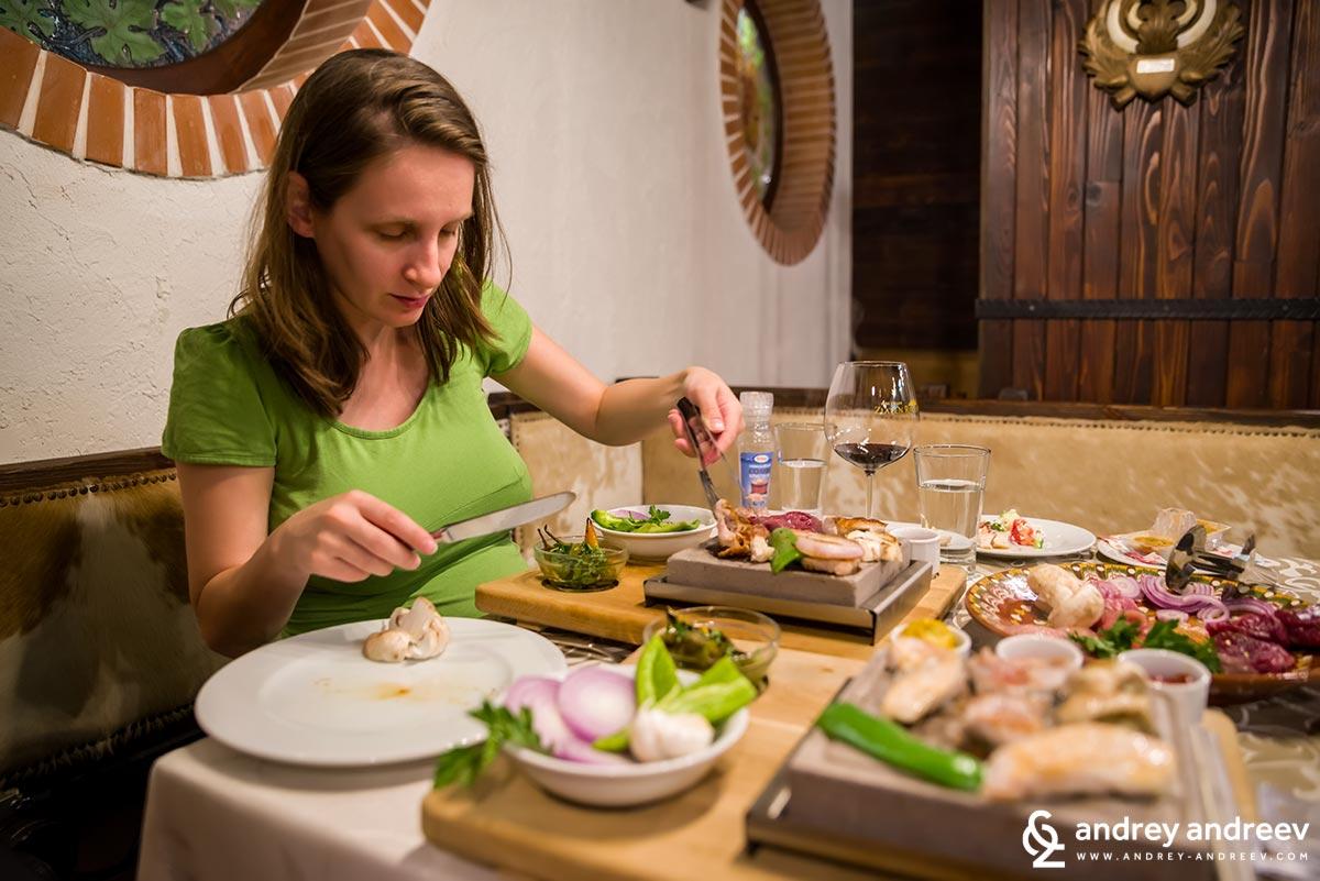 Maria cooking dinner on volcanic rocks at Zlaten Rozhen restaurant