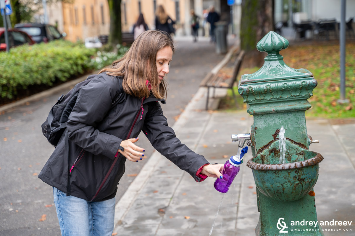 Maria fills her bottle from a fountain in Upper town Bergamo, Italy