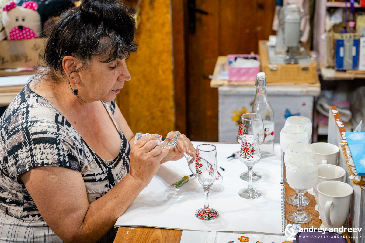 Painting Bulgarian shevitsa on wine glasses at Tinkov's workshop in Lovech