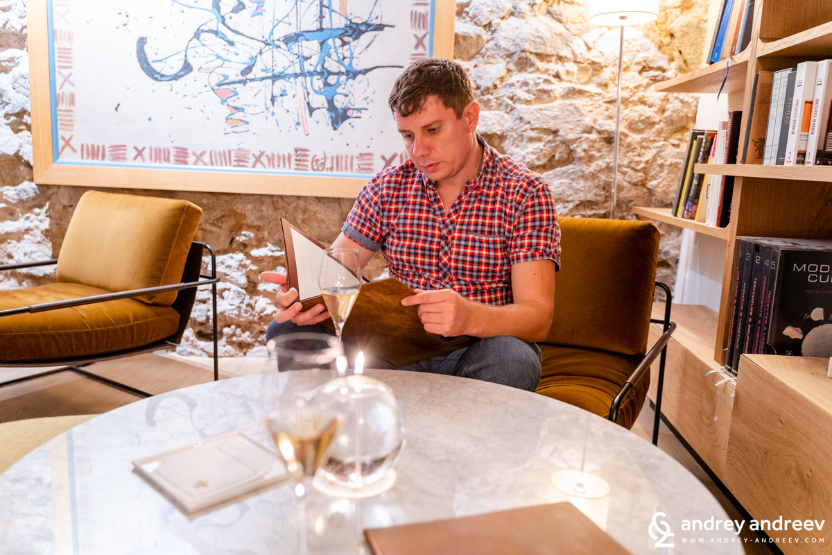 Andrey looking through the menu of La Table d'Olivier Nasti, because it is time to order