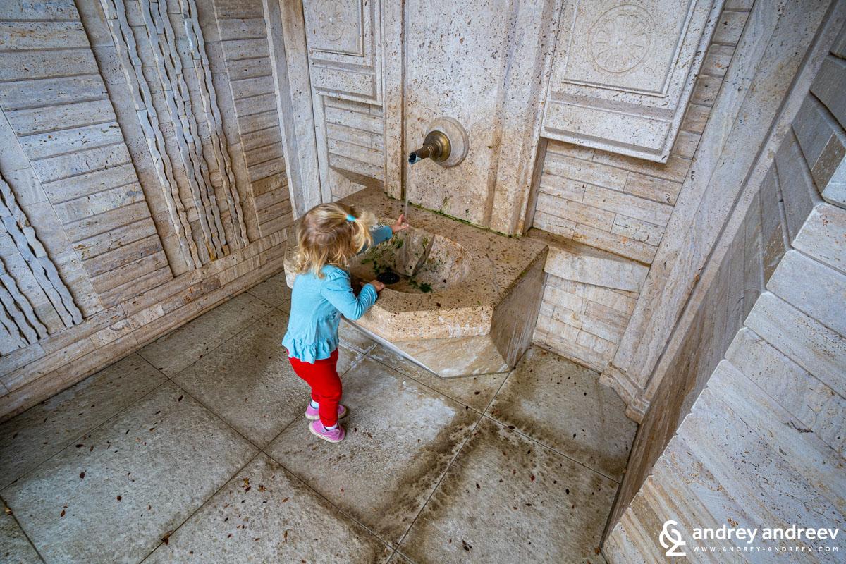 Ади си мие ръцете на чешмичката до параклиса